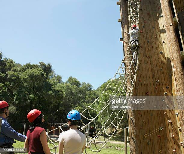 Men and women waiting to go through rope ladder obstacle