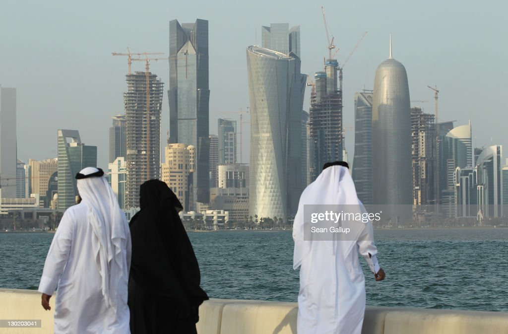 Men and women wearing traditional Qatari clothing visit the waterfront along the Persian Gulf across from new budding financial district skyscrapers...