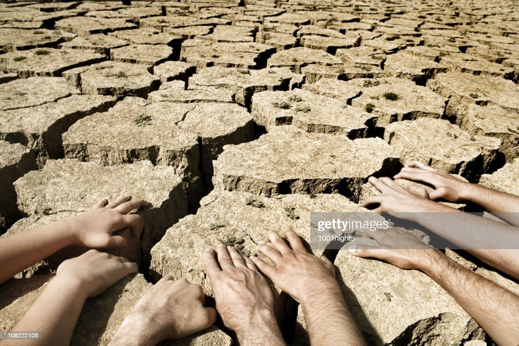 Men And Womens Hands Resting On Arid Desert Soil Stock ...