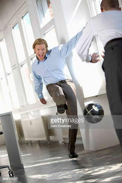 men are playing soccer in an office