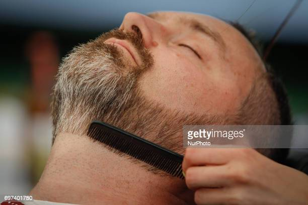 Men are seen being shaved and trimmed during a record holding bearwearer gathering in Myslecinek park on 18 June 2017