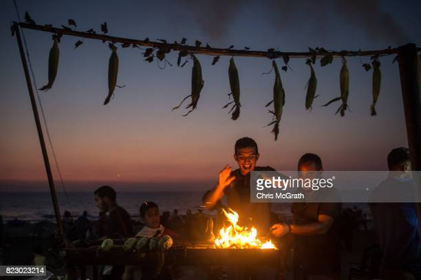 Men are seen cooking corn on the beach on July 21 2017 in Gaza City Gaza For the past ten years Gaza residents have lived with constant power...