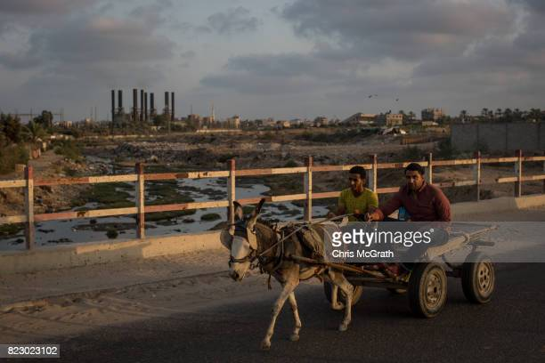 Men are seen riding a horse cart in front of Gaza's only power plant in the Nusseirat district on July 19 2017 in Gaza City Gaza For the past ten...
