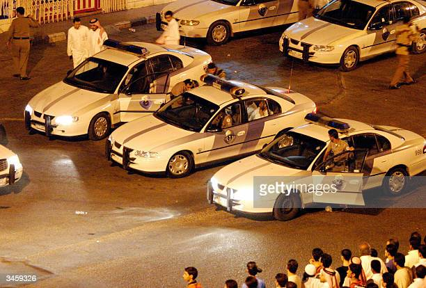 Men are seen sitting in the back of a police car after it is believed they were arrested in the port city of Jeddah late 22 April 2004 Saudi security...