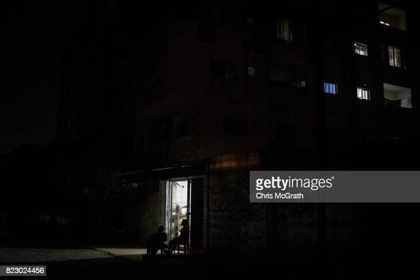 Men are seen sitting outside their shop during a power outage on July 20 2017 in Gaza City Gaza For the past ten years Gaza residents have lived with...