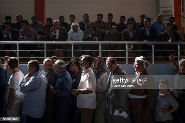 Men are seen waiting in line to cast their referendum vote at a voting station on September 25 2017 in Erbil Iraq Despite strong objection from...