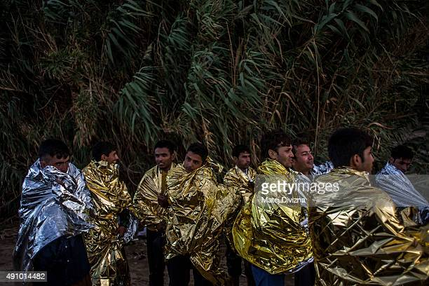 Men are wrapped with thermal blankets to shelter from cold as they arrived with other refugees on the shores of the Greek island of Lesbos after...