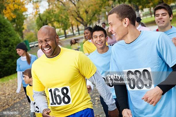 Hommes dans une course caritative rire ensemble