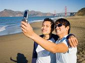 Men at beach with camera phone