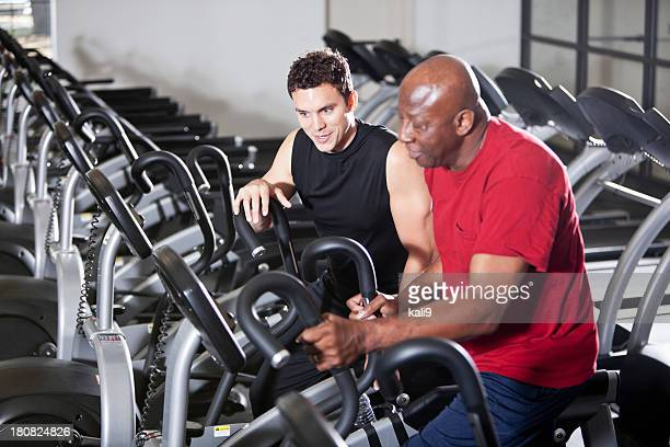 Men at health club on elliptical trainers