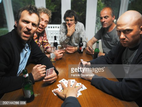 Men at table with drinks playing cards, portrait