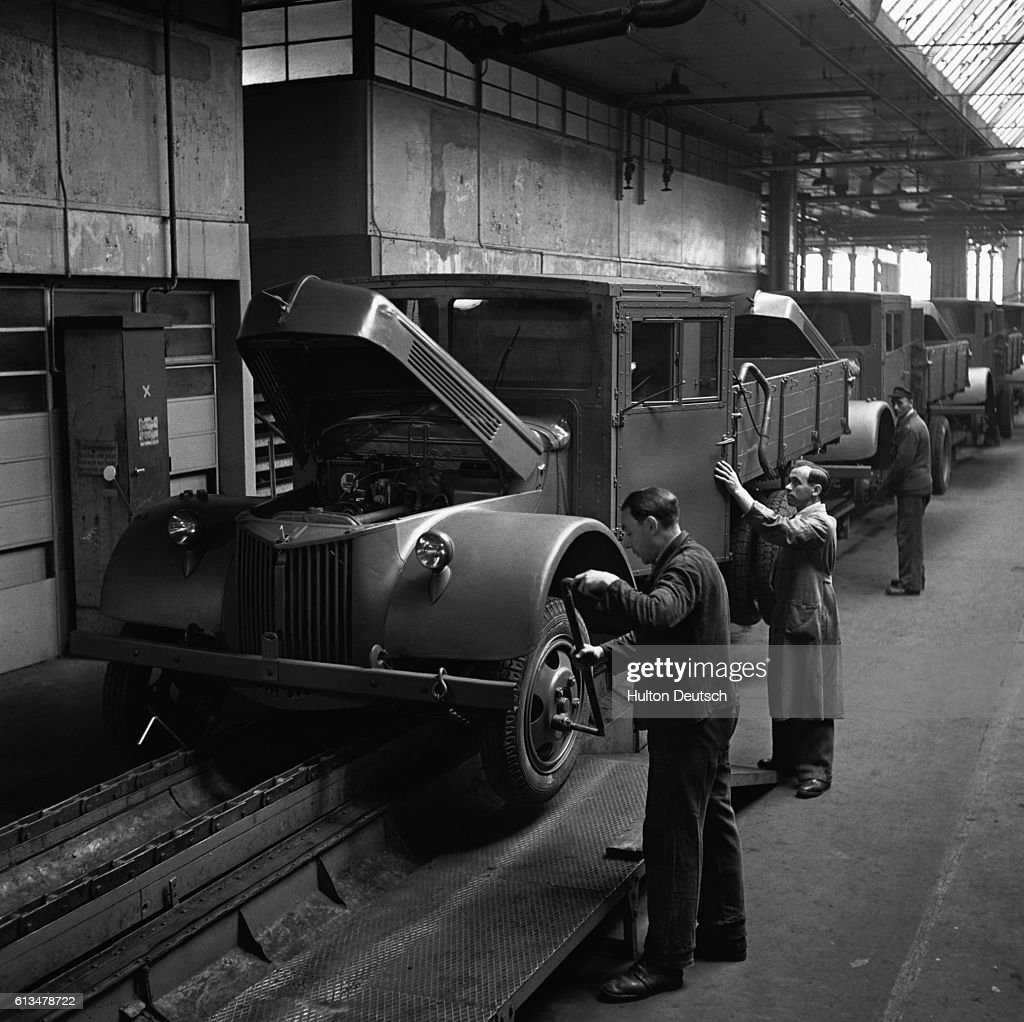Men at the Ford factory in Niehl fit the wheels of the truck to the chassis.