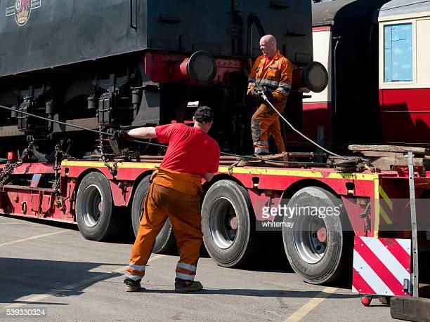 """Homme attachant un treuil ligne à un moteur à vapeur d """" offres"""