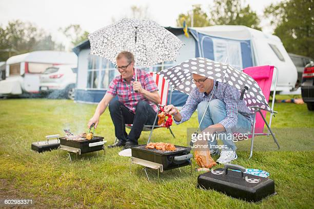 Men barbecuing in rain