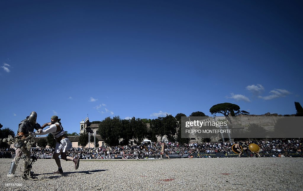 Men belonging to historical groups fight dressed as ancient Roman gladiators during a show to mark the anniversary of the legendary foundation of the eternal city in 753 B.C, in Rome on April 21, 2013. AFP PHOTO / Filippo MONTEFORTE