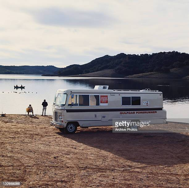Men beside motorhome looking at view of lake