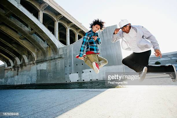 Men break dancing under overpass