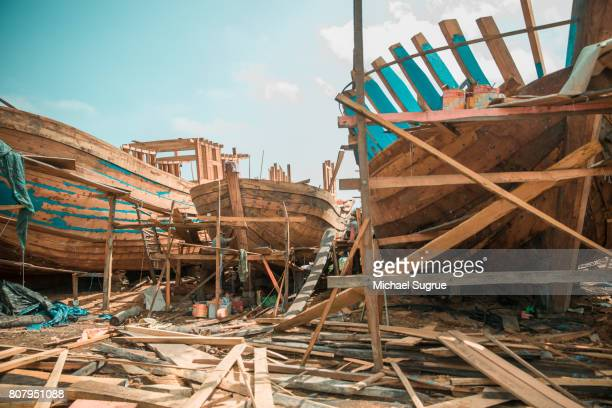 Men build a large wooden boat on the bank of the Mekong River, Vietnam.