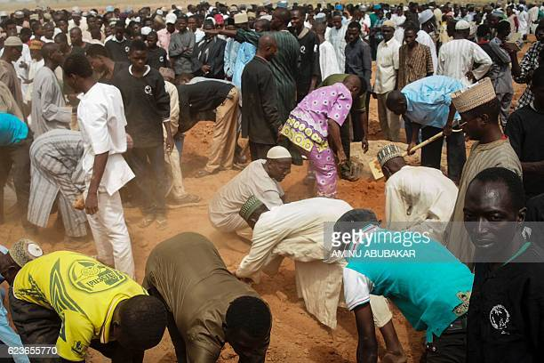 Men burry bodies during a funeral procession on November 16 2016 in Kano for some of the victims of clashes that broke out on November 14 between...