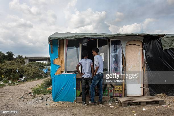 Men buy from a shop run by Afghanis at a make shift camp near the port of Calais on July 31 2015 in Calais France Strike action and daily attempts by...