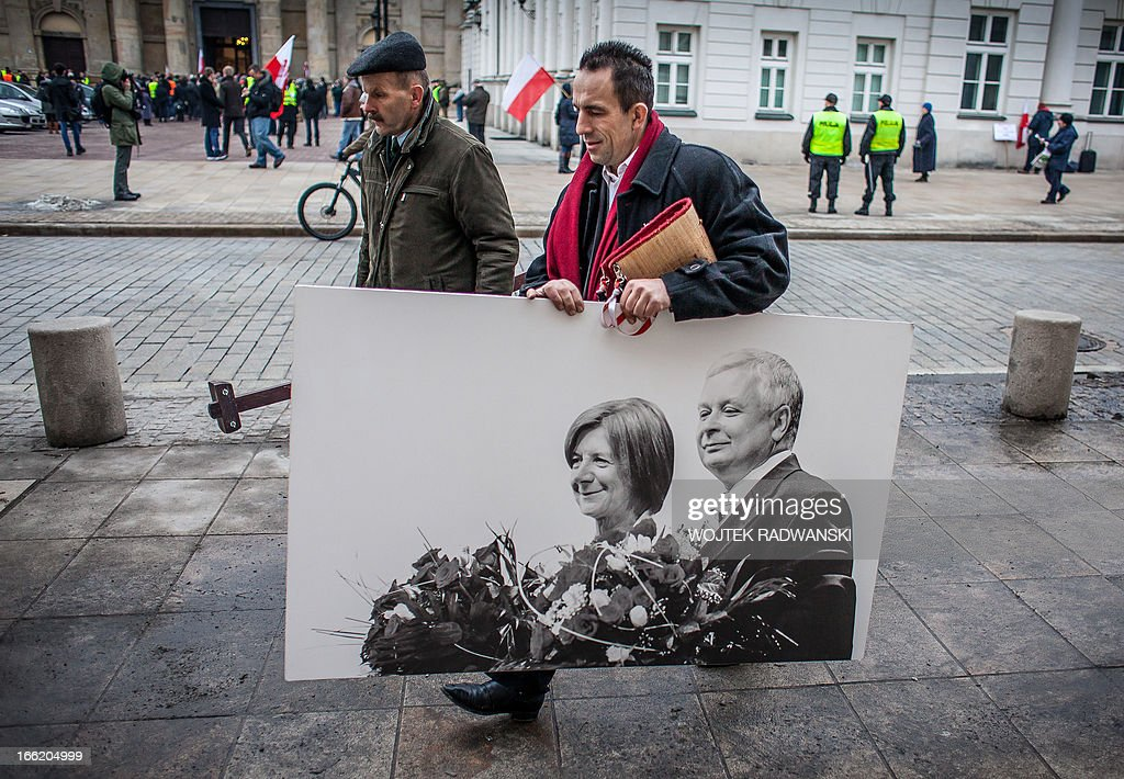 men carry a portrait of late Polish president Lech Kaczynski and his wife Maria prior to a ceremony marking the third anniversary of the crash in...
