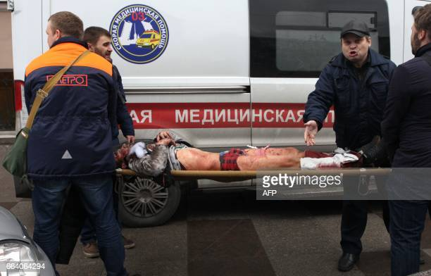 Men carry an injured person on a stretcher outside Technological Institute metro station in Saint Petersburg on April 3 2017 Around 10 people were...