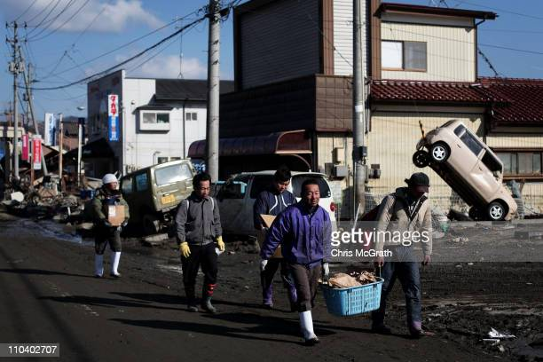Men carry belongings from destroyed homes on March 18 2011 in Ishinomaki Japan Residents have begun returning to their homes to began the massive...
