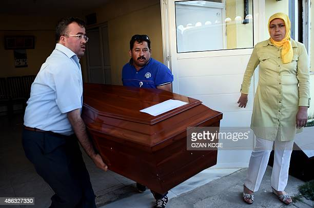 Men carry load a funeral vehicle the coffins of migrants and threeyear old Aylan Kurdi a Syrian boy whose body was washed up on a Turkish beach after...