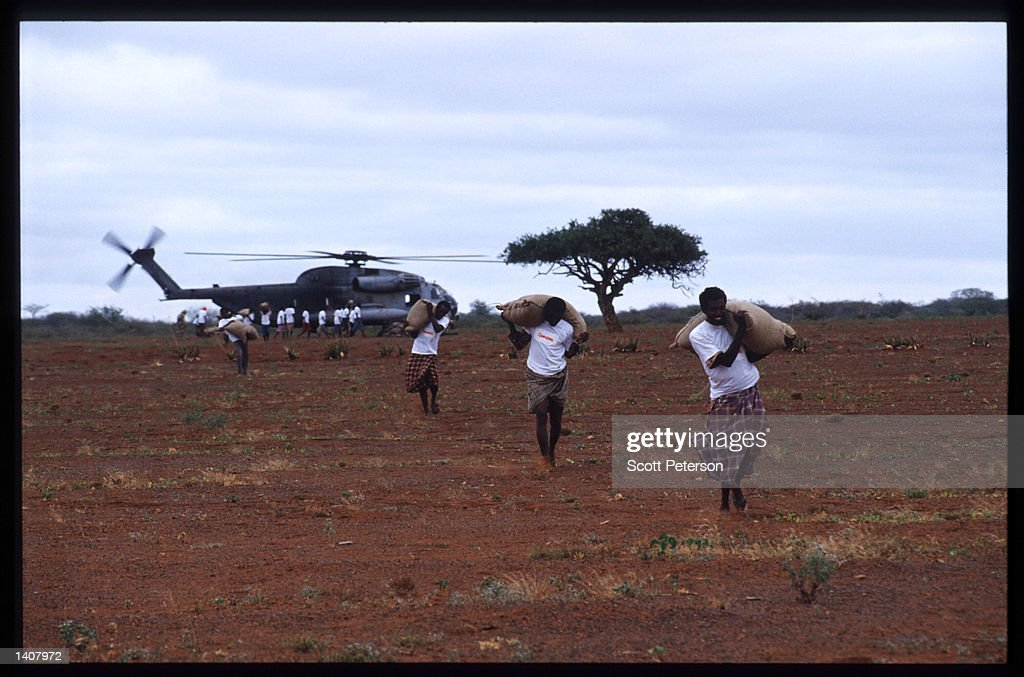 Men carry sacks of grain January 15 1993 in Labatan Jirow Somalia US troops arrived in 1992 marking the beginning of a UN peacekeeping mission aimed...
