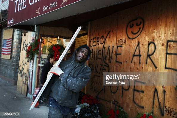 Men carry sheetrock out of The Gift is Love store near the beach in Rockaway on December 13 2012 in New York City The store which has been closed...