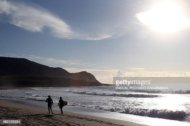 Men carry their surfs on Capo di Feno beach on December 7 2014 in Ajaccio on the French Mediterranean island of Corsica AFP PHOTO / PASCAL...