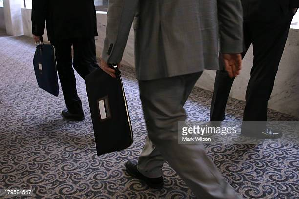 Men carrying briefcases arrive at a Senate Select Intelligence Committee closed briefing on Capitol Hill September 5 2013 in Washington DC The...
