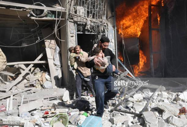 Men carrying children run out of a burning building following a barrel bomb attack reportedly dropped by government forces in the northern Syrian...