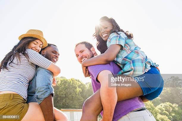 Men carrying girlfriends piggyback outdoors