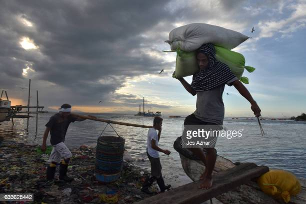 Men carrying sacks of salt to earn less than a dollar on January 27 in an impoverished village in Navotas city were a number of victims were killed...