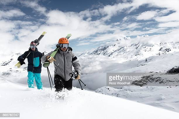 Men carrying skis in snow, Zermatt, Valais, Switzerland