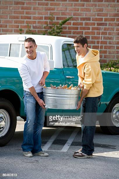 Men carrying tub of beer