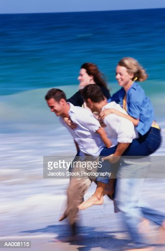 Men Carrying Women at the Beach : Stock Photo