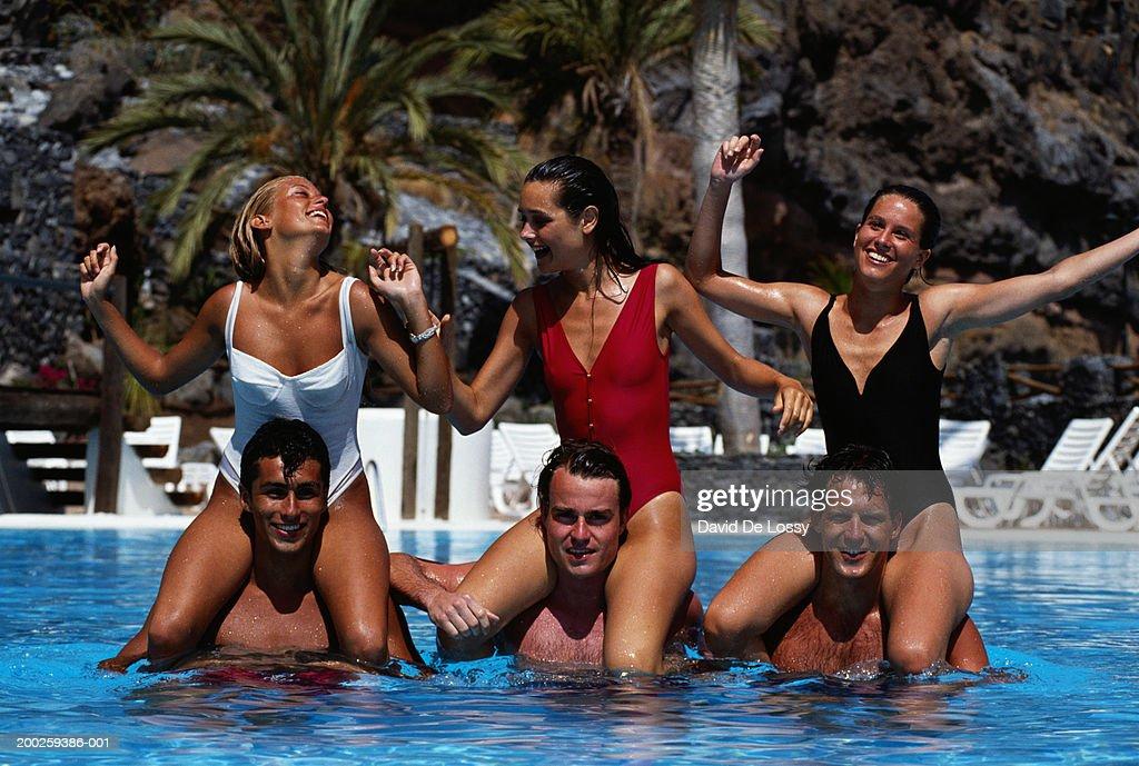 Men carrying women on shoulders in swimming pool : Stock Photo