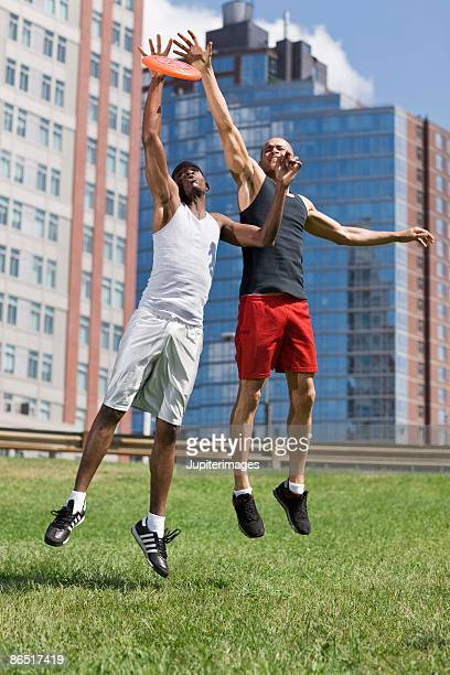 Men catching flying disc outdoors