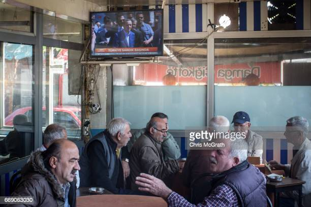 Men chat and drink chai at a teahouse while footage of Turkish President Recep Tayyip Erdogan arriving to cast his referendum vote is seen on a tv on...