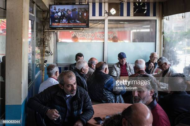 Men chat and drink chai at a teahouse while footage of Turkish President Recep Tayyip Erdogan casting his referendum vote is seen on a tv on April 16...