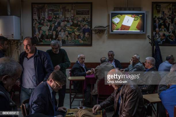 Men chat and drink chai at a teahouse while Referendum news footage plats on a tv on April 16 2017 in Istanbul Turkey Constitutional referendum...