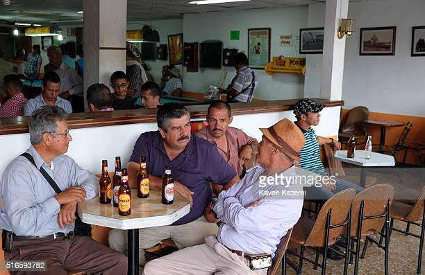 Men chat while drinking Poker beer out of bottles sat in a bar in the main town square on January 24 2016 in Filandia Colombia Filandia is a town and...