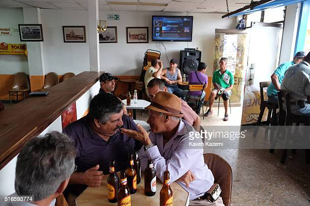 Men chat while drinking Poker beer out of bottles while sat in a bar in the main town square on January 24 2016 in Filandia Colombia Filandia is a...