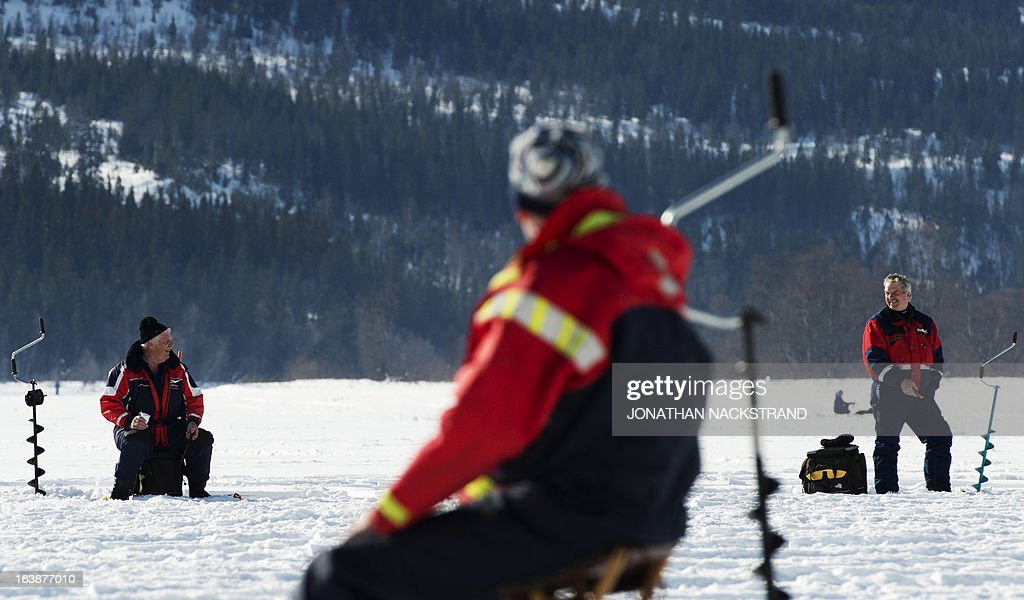 Men chat while they hold a fishing pole into a hole on the frozen Oster-Jansjon lake as he participates in an ice fishing contest in Are, Sweden on March 17, 2013.