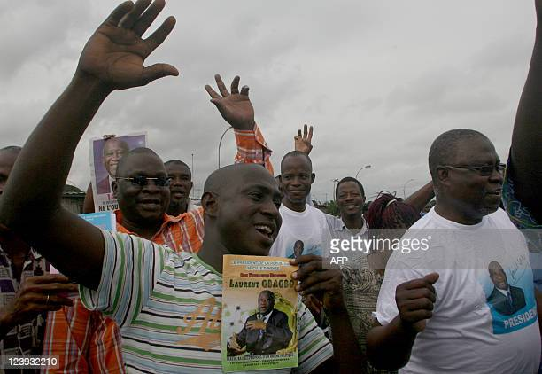Men cheer and hold a book written in honor of exIvory Coast strongman Laurent Gbagbo during a demonstration by Gbagbo supporters in the Koumassi...
