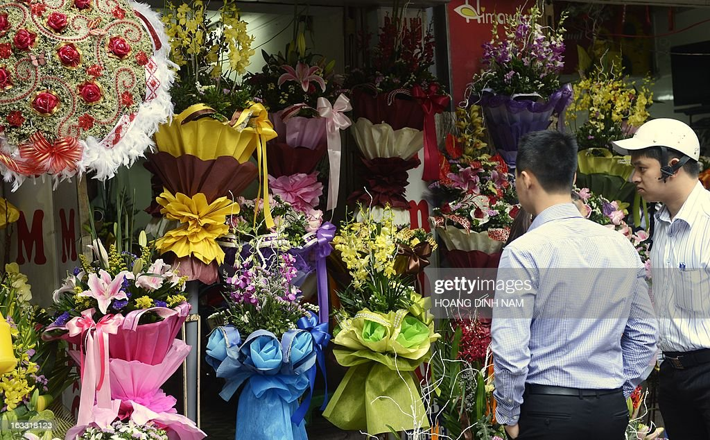Men chose flowers for their loved ones as Vietnamese celebrate the International Women's Day in Hanoi on March 8, 2013. The day is a good business opportunity for florists with a sharp rise of flowers's prices, especially for roses. AFP PHOTO/HOANG DINH Nam