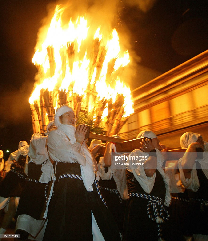 Men clad ancient armed monks costume carry the 600-kilogram portable shrine covered by 50 wooden torches during the 'Sohei (Armed Monks) Festival' at Yunoyama Hot Spring on October 8, 2012 in Komono, Mie, Japan.