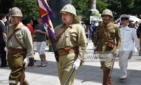 Men clad in Japanese Imperial Army and Navy uniforms march ...